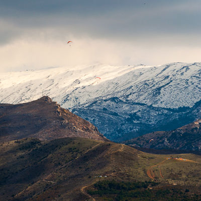 Paragliders in front of the Sierra Nevada.